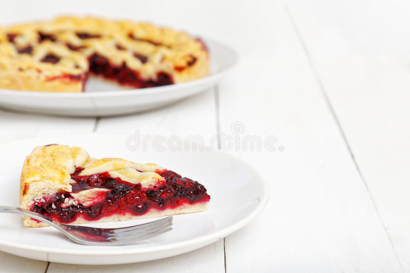 Homemade berry pie and cut a piece. Piece of homemade berry pie with cherries and raspberries on white wooden table. Shallow focus royalty free stock photos
