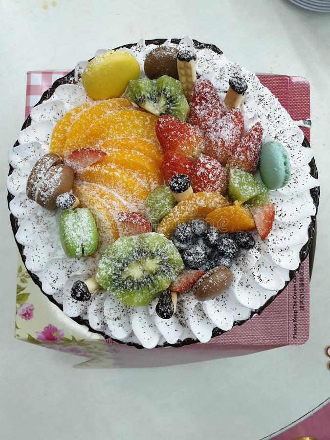 The homemade birthday cake with lots of fruits on top stock photography