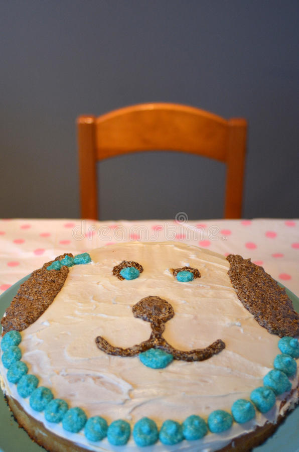 Homemade birthday cake in a shape of a dog face. On a table with empty chair and a wall background for copy space royalty free stock photos