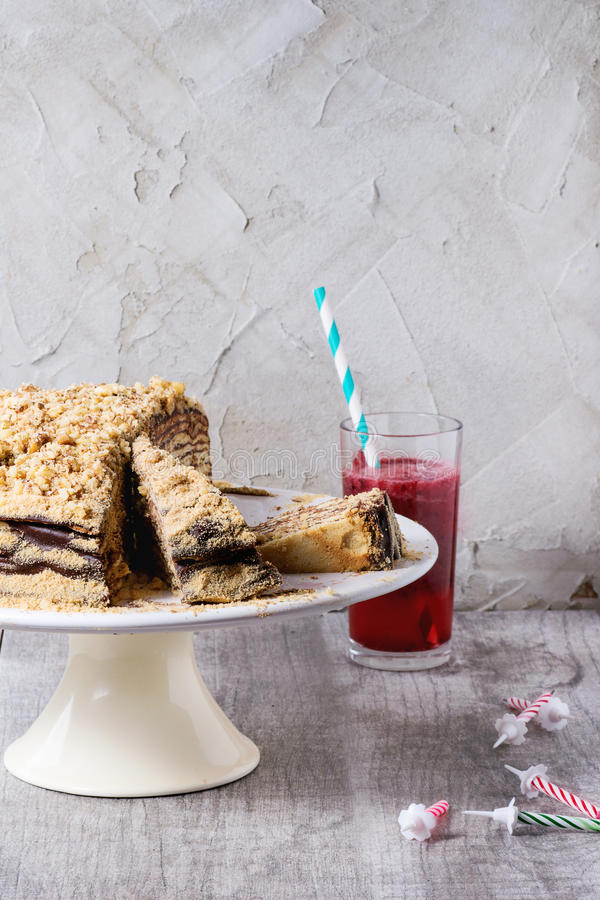 Homemade Birthday Honey Cake. Sliced Homemade Birthday Honey Cake with chocolate cream, served on white ceramic plate over white wooden table with b-day candles royalty free stock photography