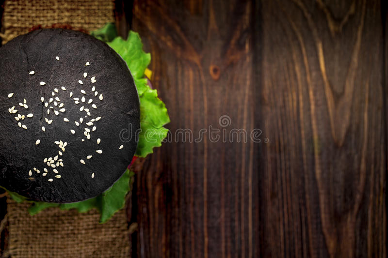 Homemade Black Burger with Cheese. Cheeseburger with black bun on dark wooden background royalty free stock photo