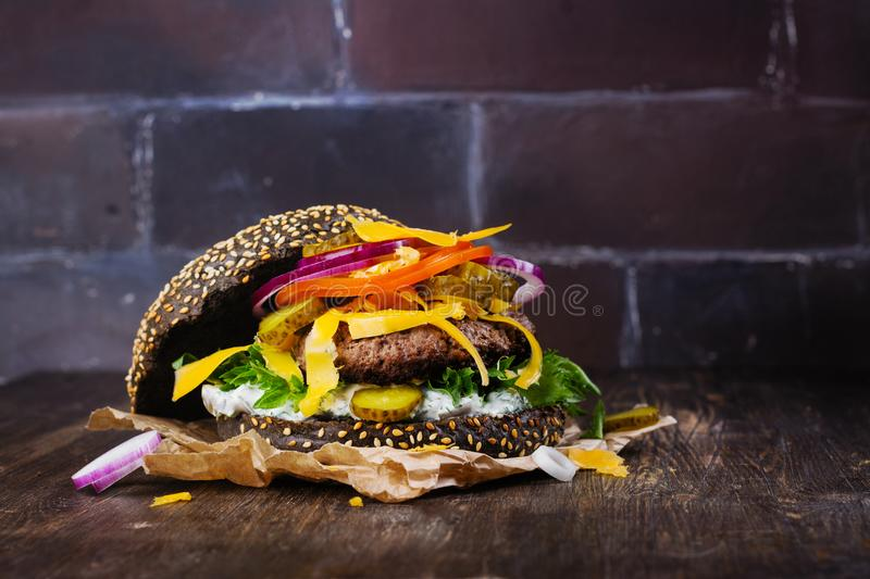 Homemade black burger with tzatziki sauce, shredded cheese and meat putty royalty free stock photography