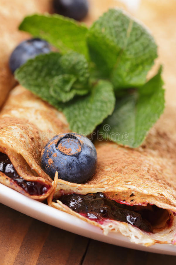 Homemade blinis with blueberries and jam, on wooden table. Homemade blinis or crepes with blueberries and jam, on wooden table stock photo