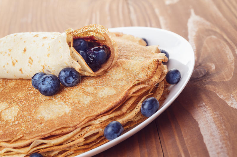 Homemade blinis or crepes with blueberries and jam toned photo. Homemade blinis or crepes with blueberries and jam, on wooden table royalty free stock photos