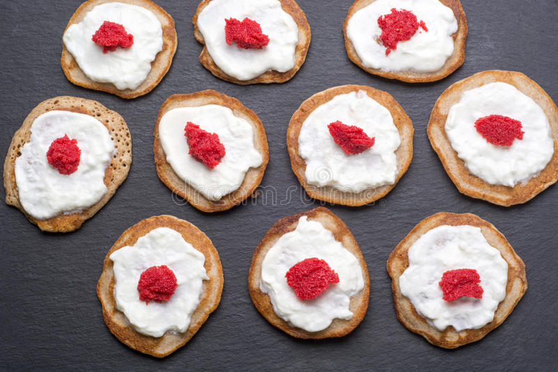 Homemade blinis with sour cream and red caviar stock photo