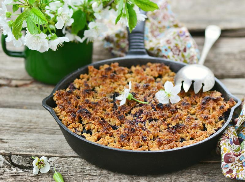 Homemade blueberry crumble on wooden table stock photo
