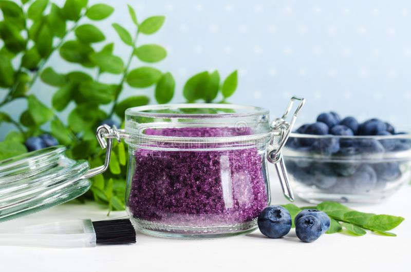 Homemade blueberry face and body sugar scrub/bath salts/foot soak in a glass jar. DIY cosmetics for natural skin care. Copy space. Homemade blueberry face and stock photo