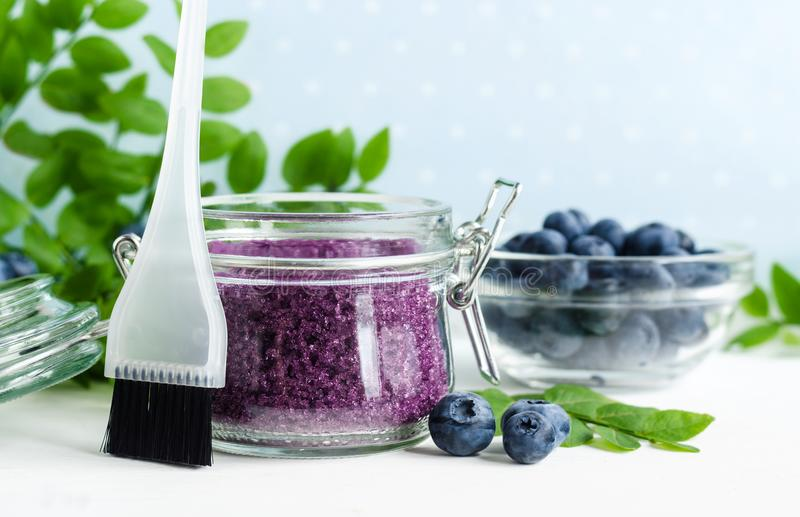 Homemade blueberry face and body sugar scrub/bath salts/foot soak in a glass jar. DIY cosmetics for natural skin care. Copy space. Homemade blueberry face and royalty free stock photo