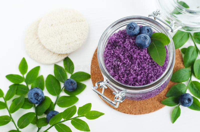 Homemade blueberry face and body sugar scrub/bath salts/foot soak in a glass jar. DIY cosmetics for natural skin care. Top view, copy space stock photos