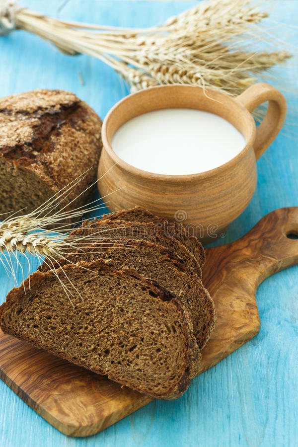 Homemade bread, milk and ripe ears of wheat on a blue wooden background royalty free stock photos