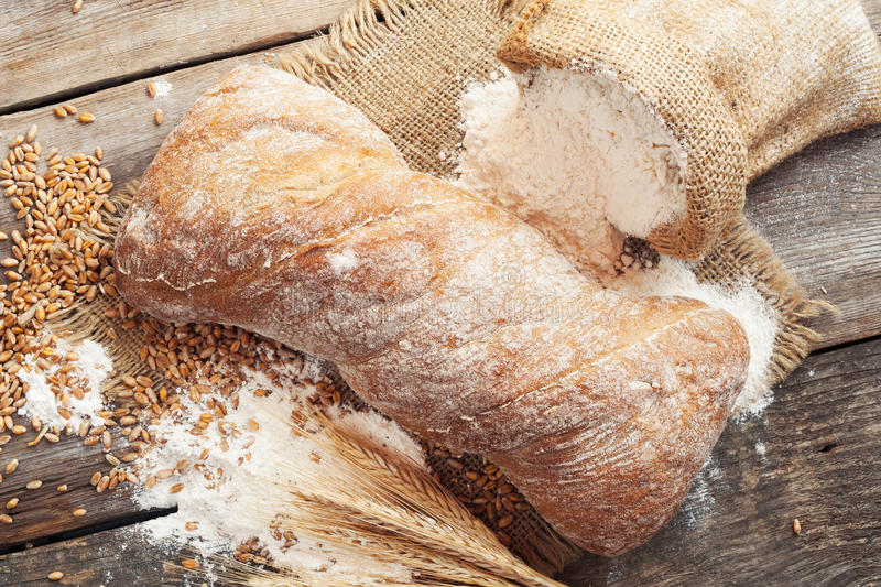 Homemade bread, sack of flour and wheat ears stock images
