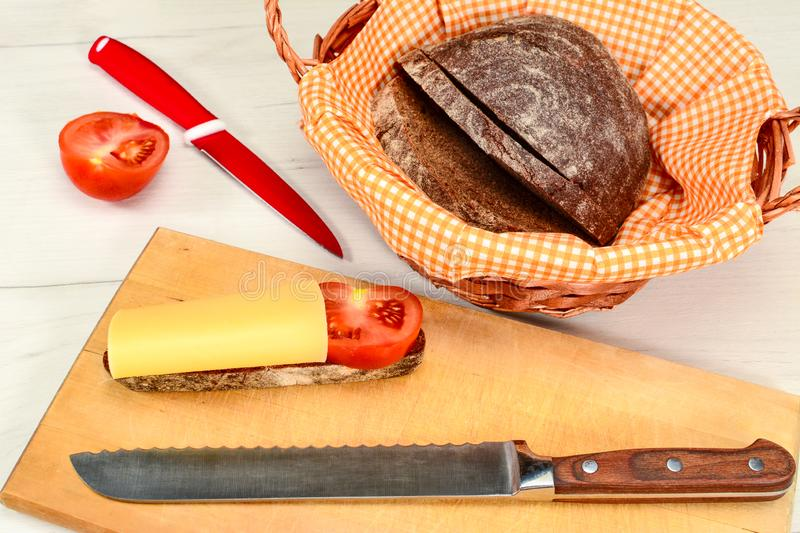 Homemade bread with tomato and cheese and the wicker basket with napkin on white table with bread knife and red knife for tomato royalty free stock photos