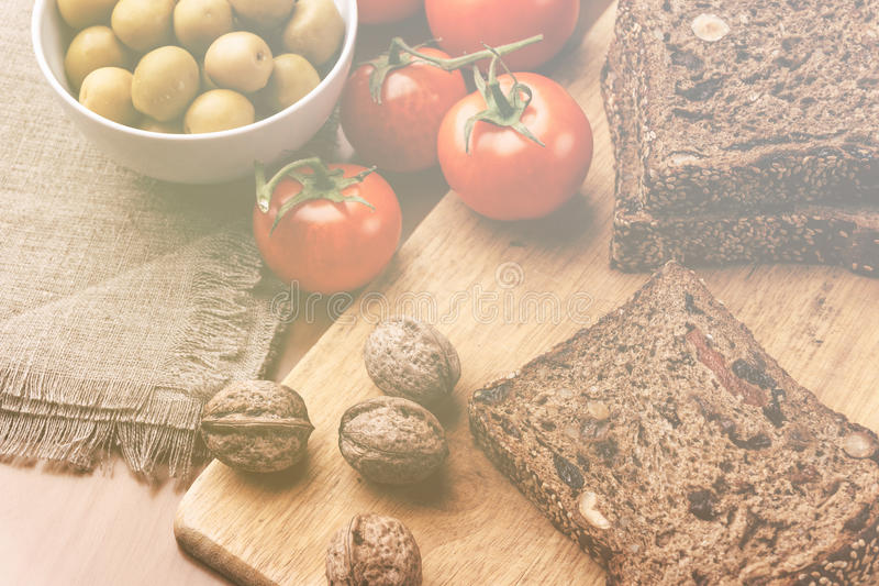 Homemade bread, walnuts, tomatoes and olives in bowl on wooden board stock photography