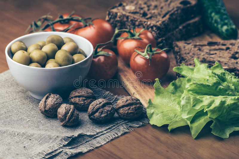 Homemade bread on wooden board, fresh tomatoes, olives in bowl, walnuts royalty free stock photo