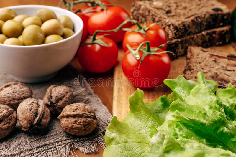 Homemade bread on wooden board, fresh tomatoes, olives in bowl, walnuts stock image