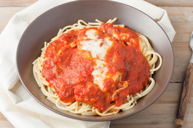 Homemade breaded cutlet in tomato sauce and melted cheese over spagetti stock images