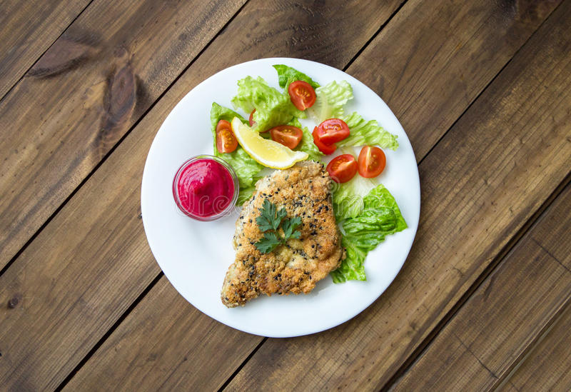 Homemade Breaded Schnitzel with salad and berry sauce stock image