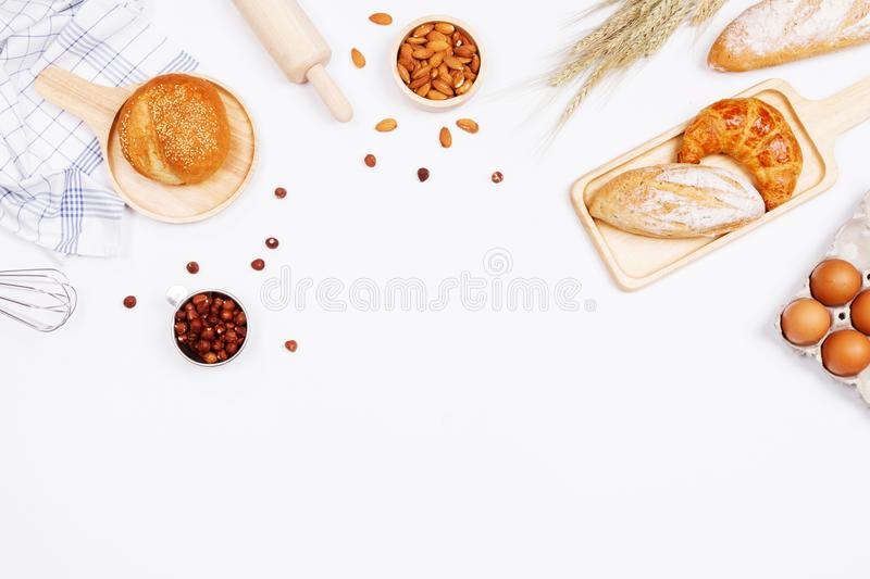 Homemade breads or bun, croissant and bakery ingredients, flour, almond nuts, hazelnuts, eggs on white background, Bakery stock image