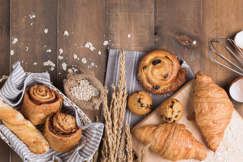 Homemade breads or bun on wood background. Croissant puff cinnamon, breakfast food royalty free stock image