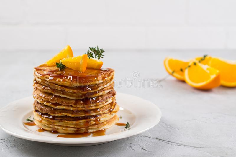 Homemade breakfast or brunch: american style pancakes served with orange and sprinkled syrup stock photography