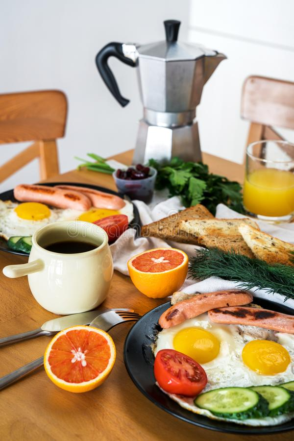 Homemade breakfast with fried eggs toast sausages fruits vegetables orange juice and coffee stock photography