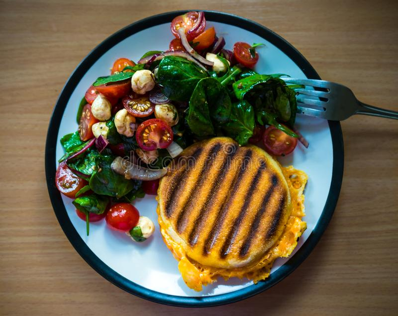 Homemade Breakfast grilled English miffin Sandwich served with side salad: cherry tomatoes, pearl mozzarella and spinach royalty free stock photos