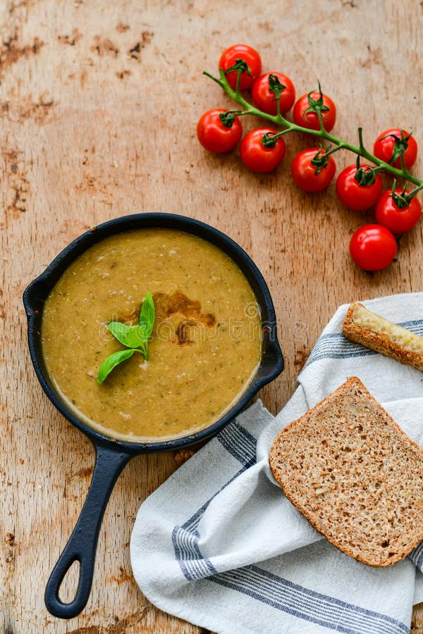 Homemade Brown Lentil cream soup. Homemade Brown Lentil Soup with Carrots Onions and Tomatos and cheese soldiers and bread on wooden rustic backgrouns royalty free stock photos