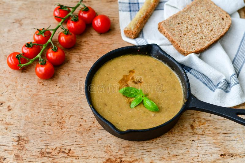 Homemade Brown Lentil cream soup. Homemade Brown Lentil Soup with Carrots Onions and Tomatos and cheese soldiers and bread on wooden rustic backgrouns stock photo