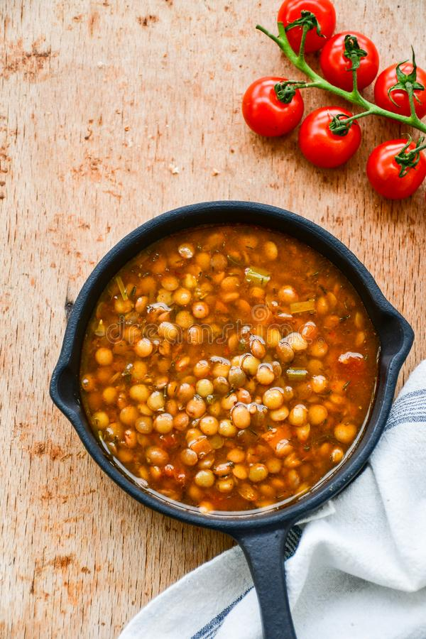 Homemade Brown Lentil soup. With Carrots Onions and Tomatos and cheese soldiers and bread on wooden rustic backgrouns royalty free stock photo