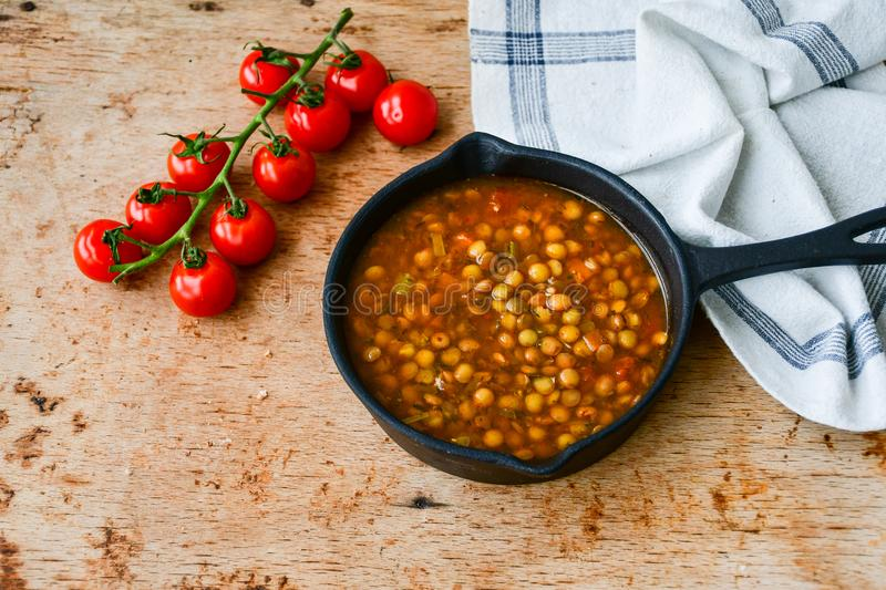 Homemade Brown Lentil soup. With Carrots Onions and Tomatos and cheese soldiers and bread on wooden rustic backgrouns stock photography