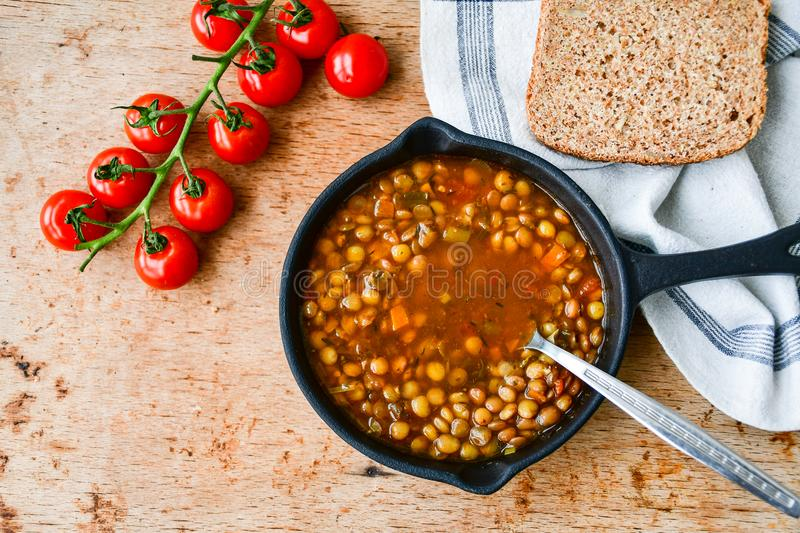 Homemade Brown Lentil soup. With Carrots Onions and Tomatos and cheese soldiers and bread on wooden rustic backgrouns royalty free stock image