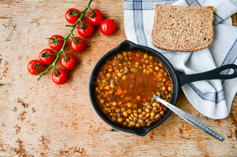 Homemade Brown Lentil soup. With Carrots Onions and Tomatos and cheese soldiers and bread on wooden rustic backgrouns stock photo