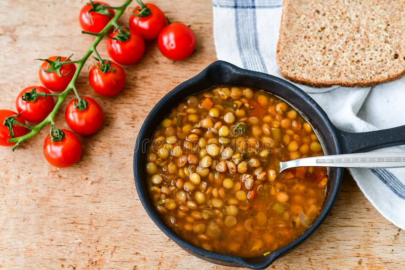Homemade Brown Lentil soup. With Carrots Onions and Tomatos and cheese soldiers and bread on wooden rustic backgrouns stock image