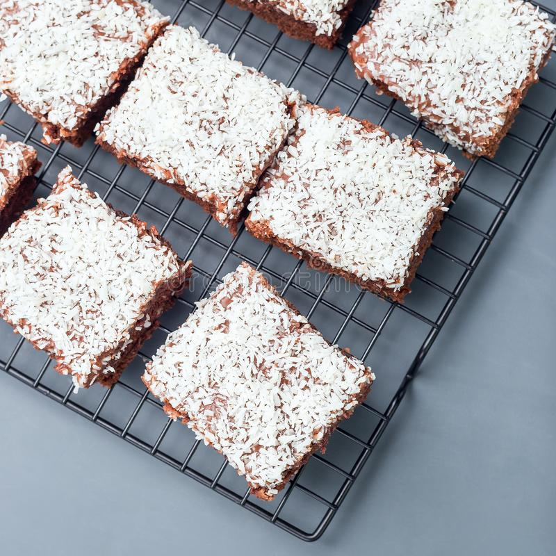 Homemade brownie with coconut flakes, swedish dessert Karleksmums, cut in square servings, on cooling rack, top view, square. Homemade brownie with coconut royalty free stock image