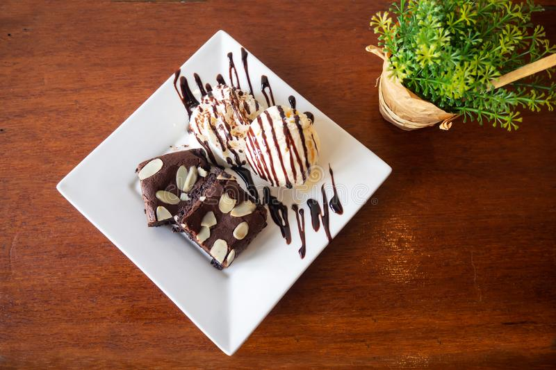 Homemade brownie served with vanila icecream and whipping cream. Sweet dessert for chocolate flavor royalty free stock photography