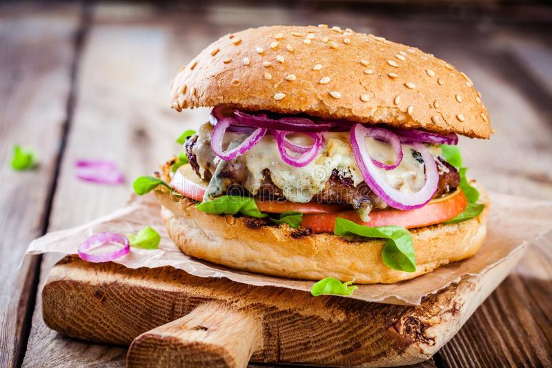 Homemade burger with beef cutlet, apple, lettuce, onion and blue cheese. On wooden table royalty free stock image