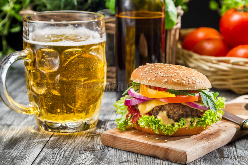 Homemade burger and a cold beer. Closeup of homemade burger and a cold beer on old wooden table royalty free stock image