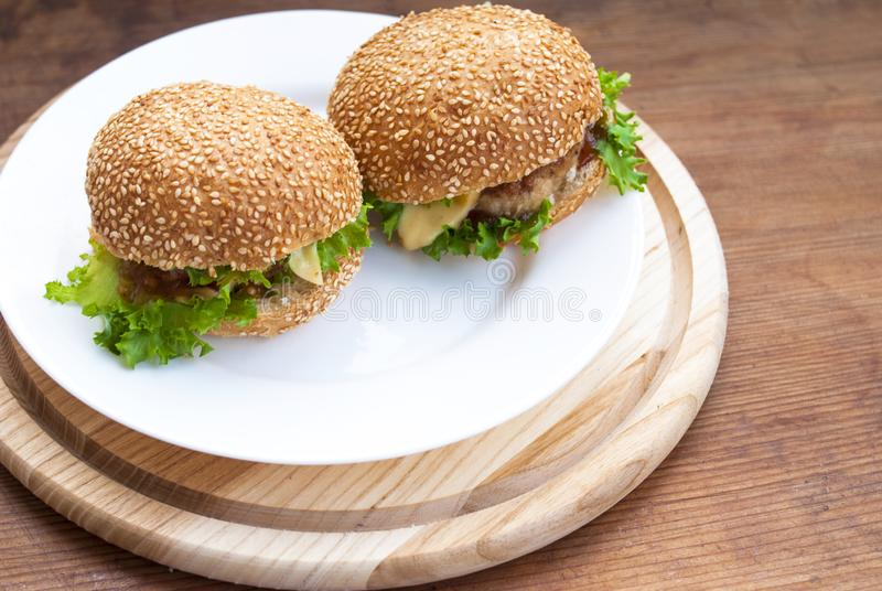 Homemade burger with cutlet, cheese, sauce, herbs and a bun. Close-up. Wood background stock image