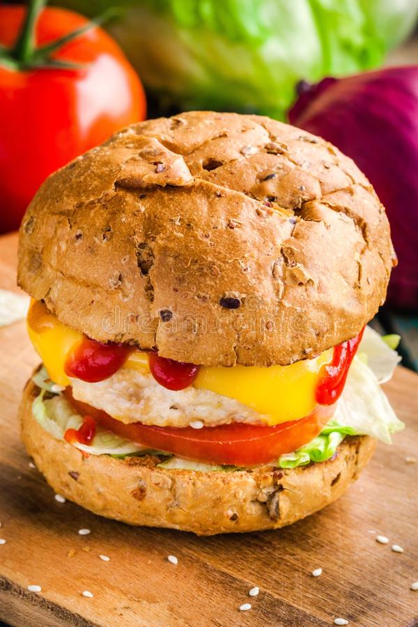 Homemade burger with fresh vegetables and chicken cutlet royalty free stock photos