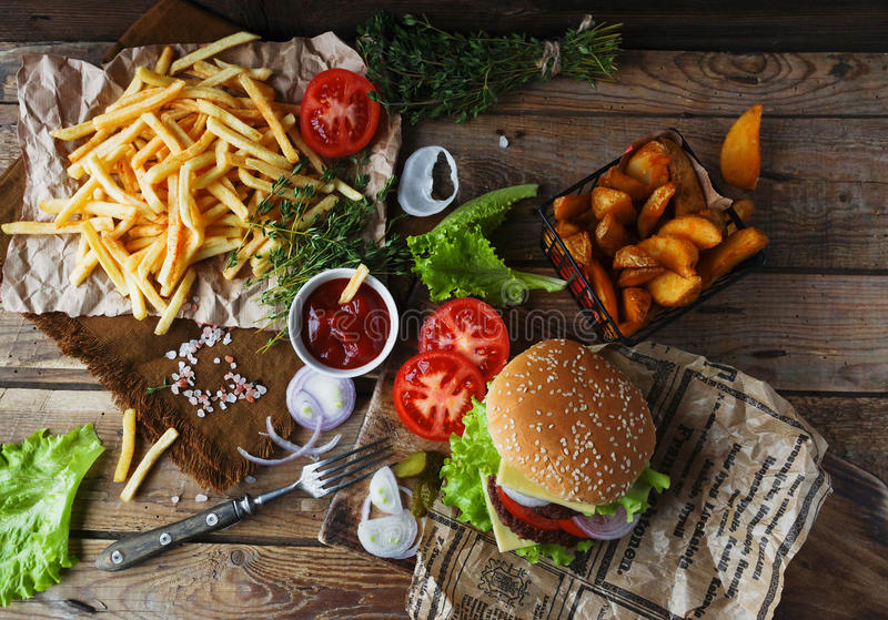 Homemade burger, fried potatoes, french fries, fast food set. Delicious homemade burger, fried potatoes, fresh tomatoes, lettuce, onions, cheese on rustic wooden stock image
