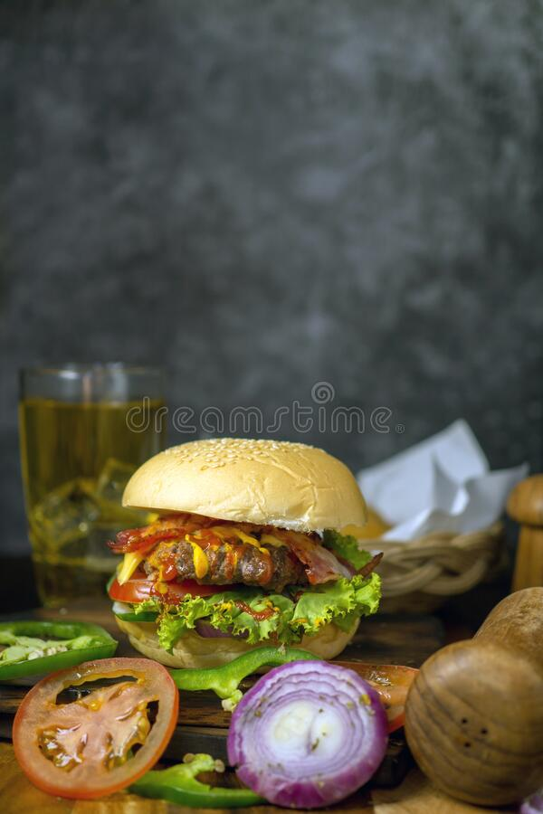 Homemade burgers with beer and cola made of bacon, pork, tomato, lettuce, onion, cheese and spices on wooden background royalty free stock photo