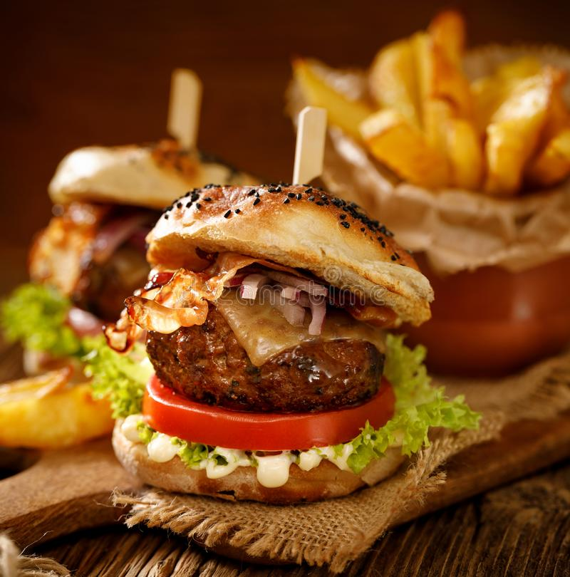 Homemade burgers with grilled bacon, red onion, fresh lettuce, cucumber pickles, tomato and aromatic mayonnaise sauce on a wooden royalty free stock photo
