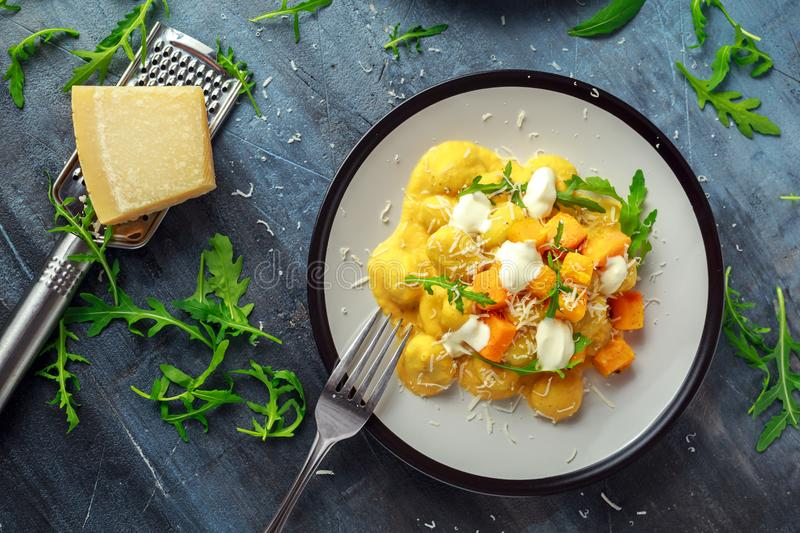 Homemade Butternut squash gnocchi with wild rocket and parmesan, ricotta cheese.  royalty free stock image