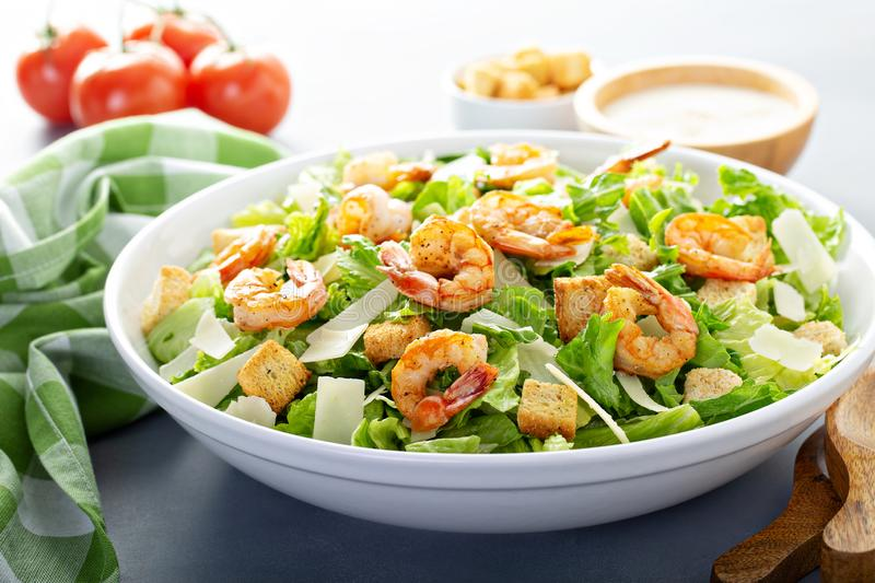 Homemade caesar salad with shrimp. And dressing on the side stock image