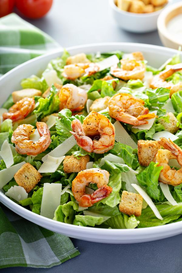Homemade caesar salad with shrimp. And dressing on the side stock images