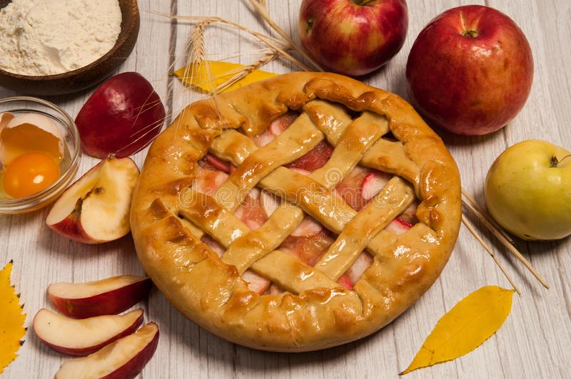 Delicious Apple pie, red and yellow apples, egg, flour, yellow leaves on wooden background. Homemade cake. Delicious Apple pie, red and yellow apples, egg stock photo