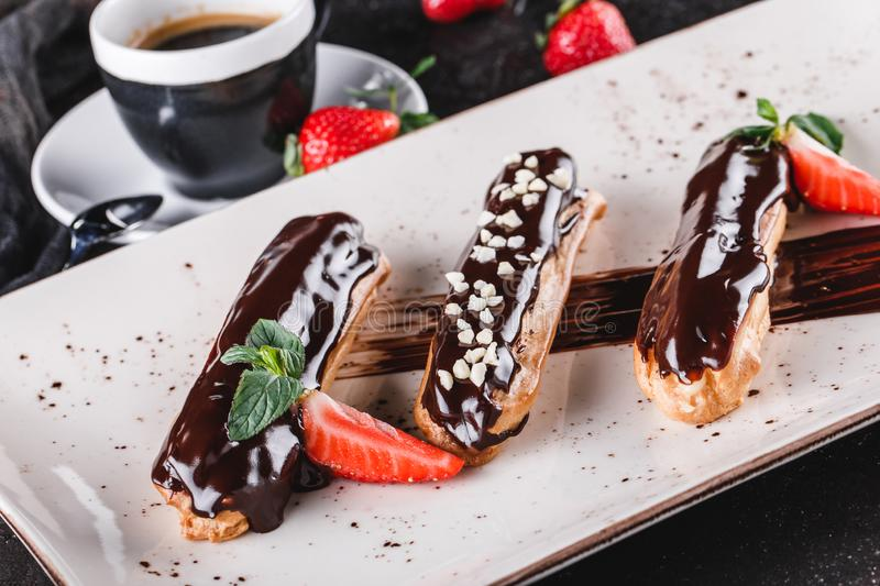 Homemade cake eclairs or profiteroles with custard, chocolate and strawberries on dark background served with cup of coffee royalty free stock photography