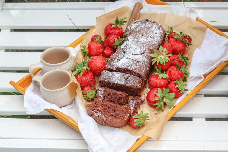 Homemade cake and fresh strawberries  on a white garden bench royalty free stock photo