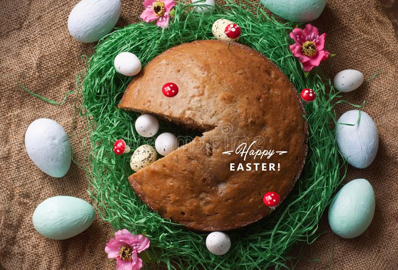 Homemade cake in a nest from fake green grass and Easter eggs isolated on sackcloth texture. Funny Pack man face from cake royalty free stock image