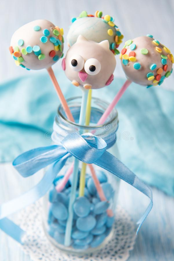 Homemade cake pops one in the owl shape with multi coloured sprinkles, sweet food for kids. Homemade cake pops one in the cute owl shape with multi coloured royalty free stock images